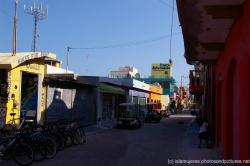 Looking down a street stands a French Bistro and other shops on Isla Mujeres.jpg